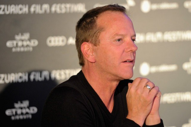 Kiefer Sutherland stares ahead and holds hands together in front of black backdrop that promoting the Zurich Film Festival.