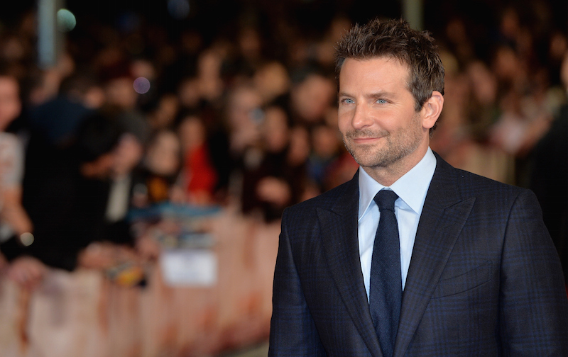 Bradley Cooper is smiling on the red carpet.