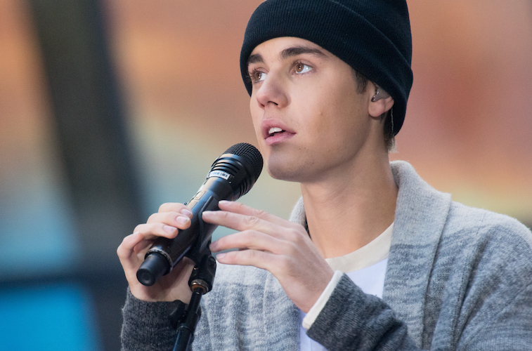 Justin Bieber holds a microphone while performing a song.