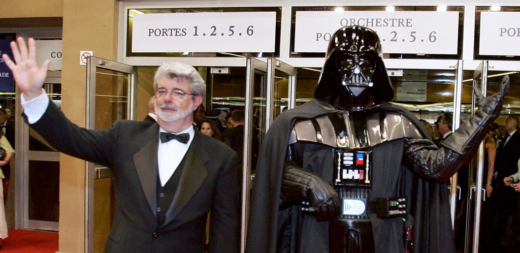 George Lucas in a tux waving next to a figurine of Darth Vader waving
