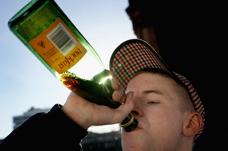 A young man chugs alcohol, which is a cause of several types of cancer