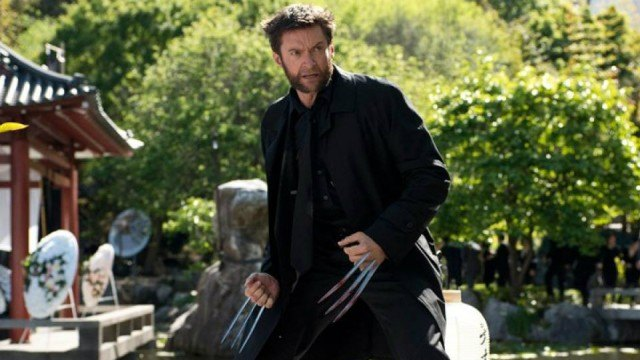 Wolverine with his claws out, wearing a black trench coat