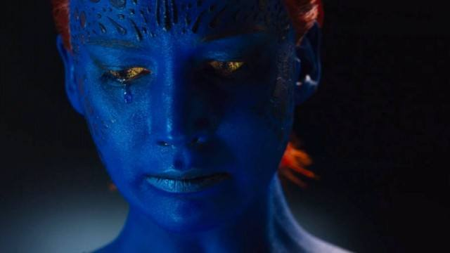 Jennifer Lawrence as Mystique, with blue skin and orange hair, sadly looking down and to her right.