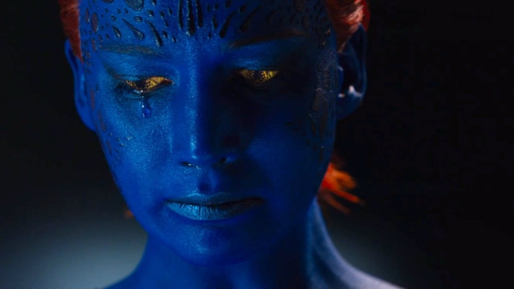 Jennifer Lawrence as Mystique, with blue skin and orange hair, sadly looking down and to her right