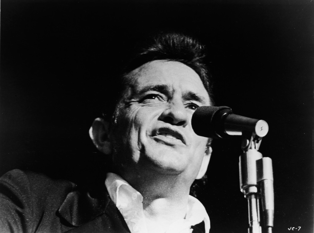 Johnny Cash sings into a microphone.