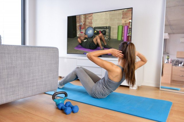 woman working out in front of TV on yoga mat
