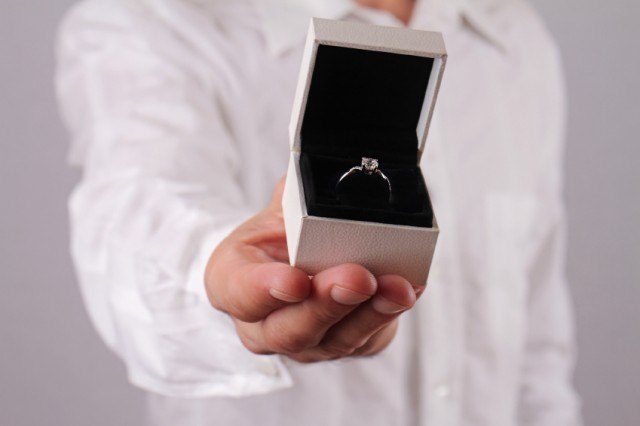 A man holds up an engagement ring.