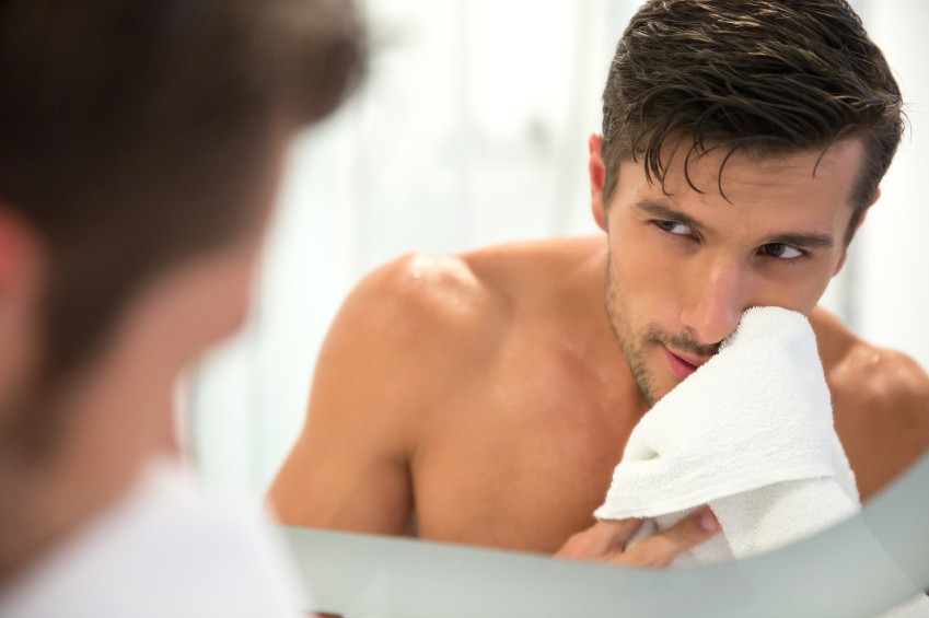 A man inspects himself in the mirror