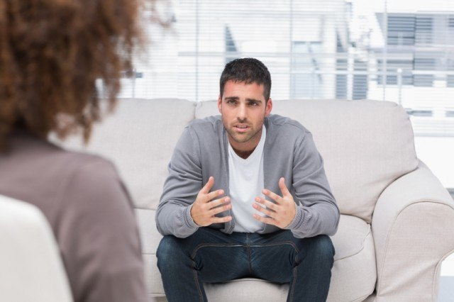 A man sits on a couch across from a therapist as they talk to each other.