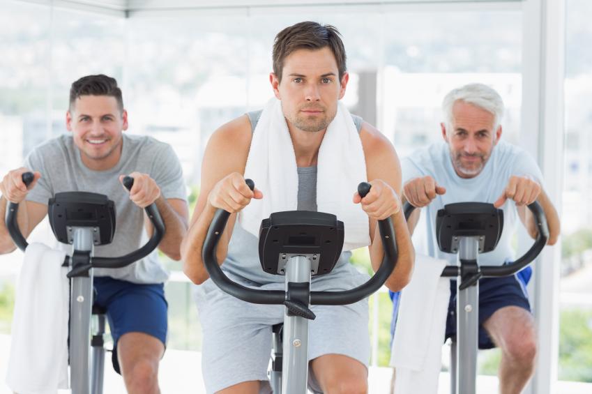 Men on exercise bikes at gym