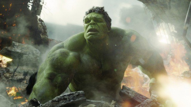 The Hulk in the middle off an explosion, looking off into the distance