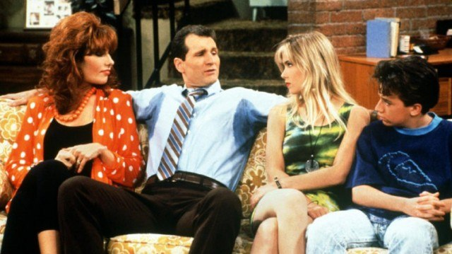 The cast of 'Married... with Children' sit together on a living room couch