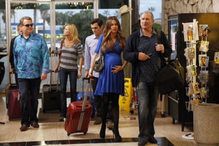 The adult cast on Modern Family pull luggage through an airport
