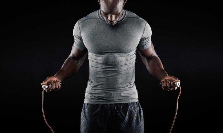 Muscular man in light grey shirt jumping rope