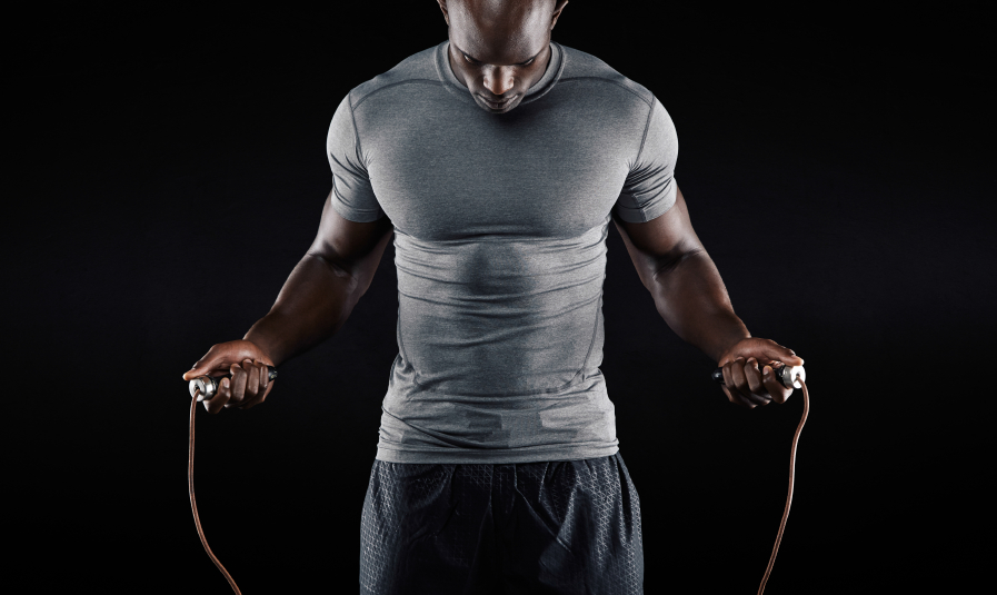 Muscular man in light grey shirt jumping rope