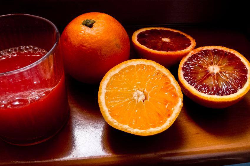 blood orange juice and sliced oranges on a wooden background