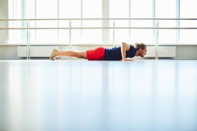 man in the bottom phase of a push-up in an empty room