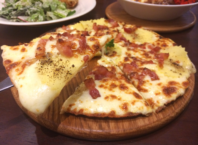 slice of bacon and potato pizza on a wooden pizza peel