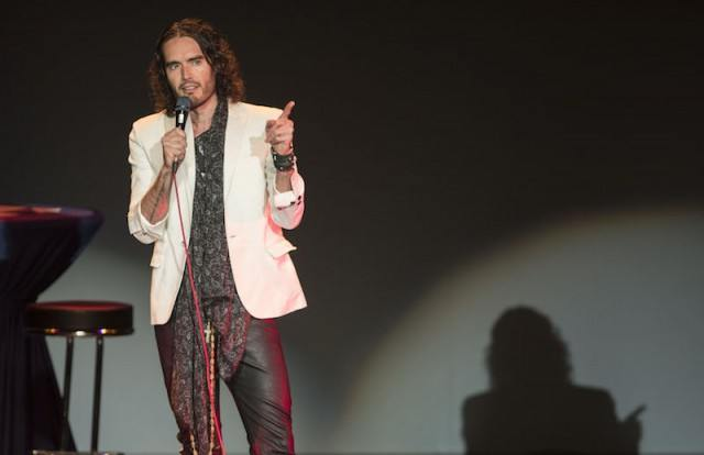 Russell Brand is talking on stage and holding a microphone.