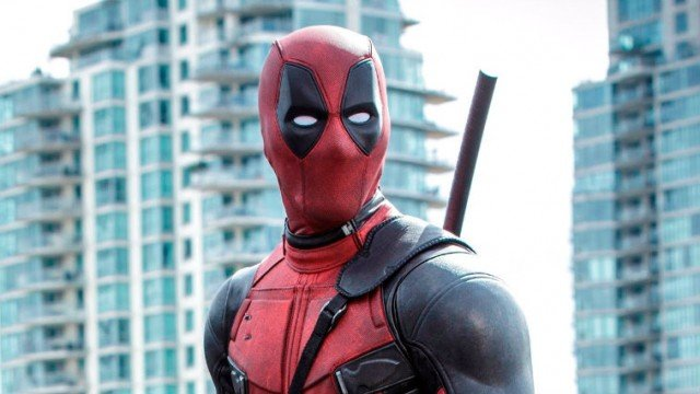 Deadpool standing in front of several tall buildings.