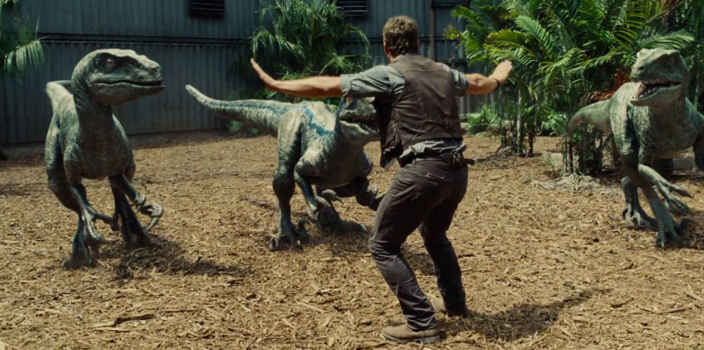 Chris Pratt with his arms out, as three raptors slowly approach him