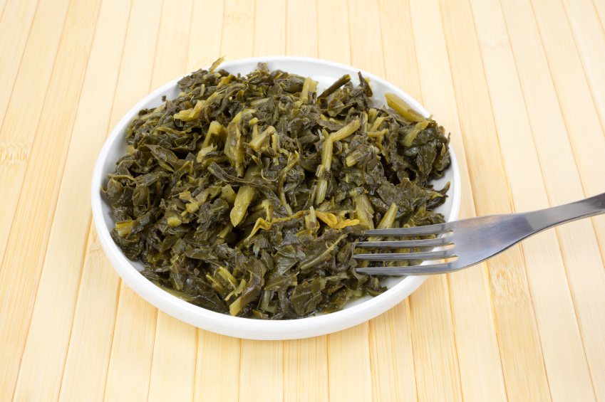 a serving of braised collard greens in a white bowl