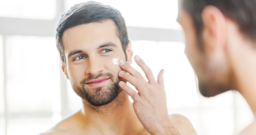 man putting moisturizer on his skin to look more youthful