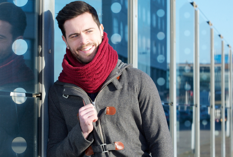 Smiling man with jacket and scarf relaxing outdoors