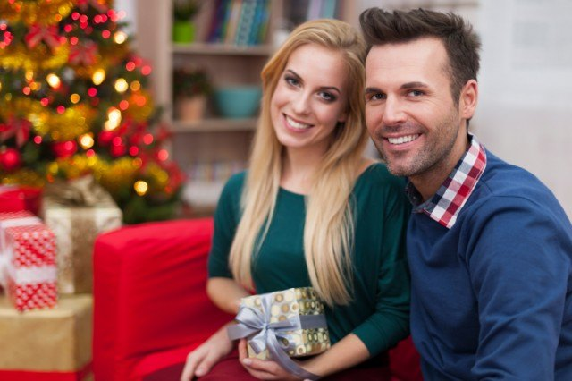 happy couple exchanging gifts during the holidays