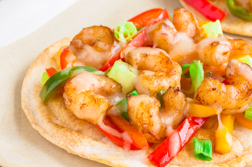 cutting into a spicy shrimp pizza with scallions and bell peppers