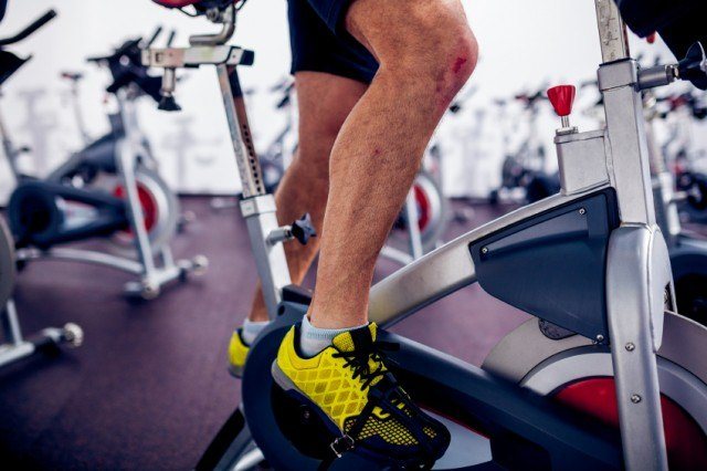 close-up of man riding a stationary bike at the gym
