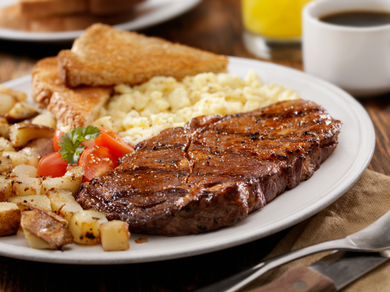 steak and scrambled eggs with toast and home fries on a white plate
