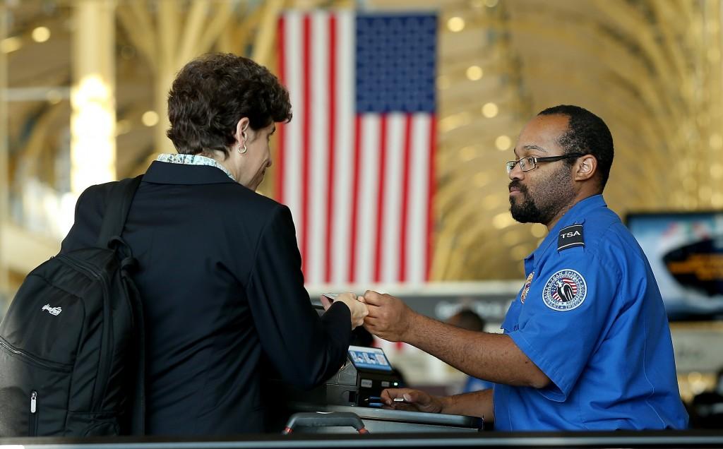 A TSA security employee assists a passenger