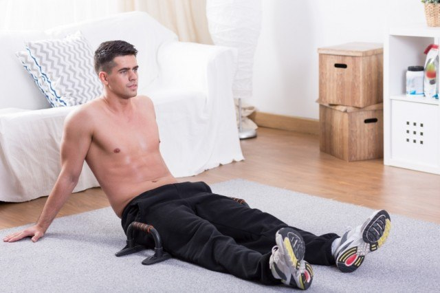 A man sits on a mat while working out at home.