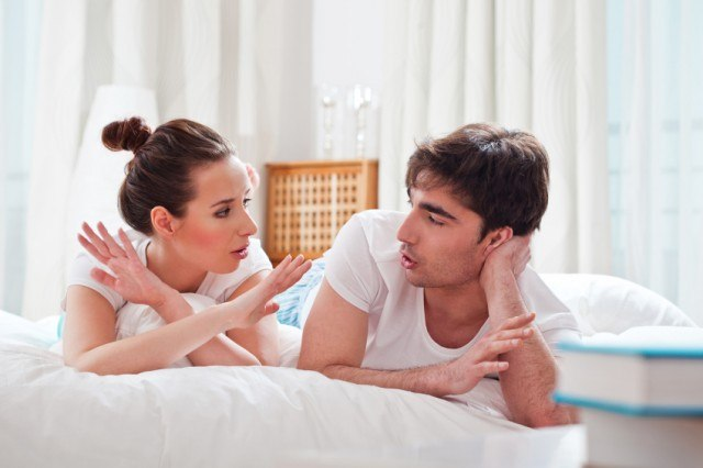 a heterosexual couple lie on their stomachs in bed while they have a discussion