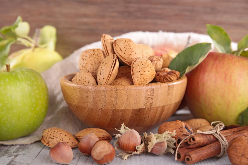 bowl of unshelled almonds with a red and reen apple
