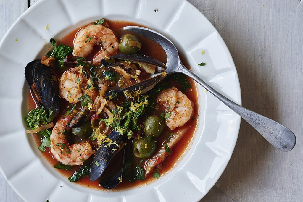 seafood stew with olives, mussels, shrimp, and broccoli rabe in a white bowl