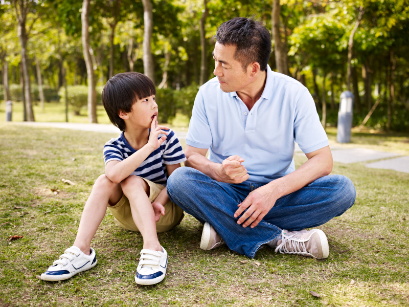 asian father and son sitting on grass
