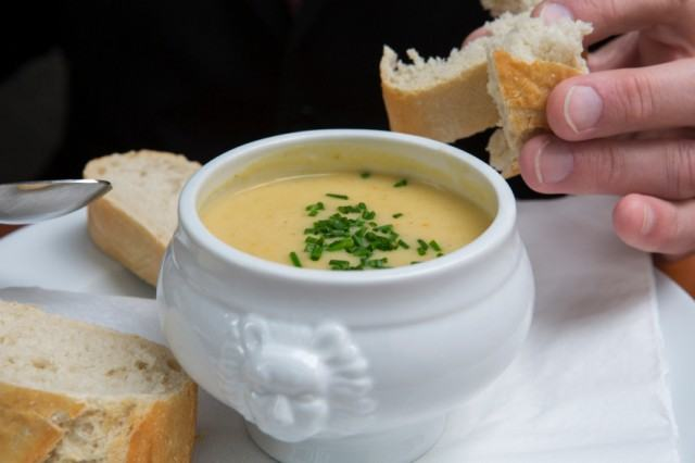 hand dipping bread into a bowl of potato soup