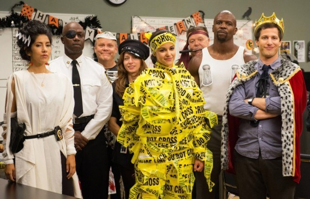 The cast wearing halloween costumes in their office.