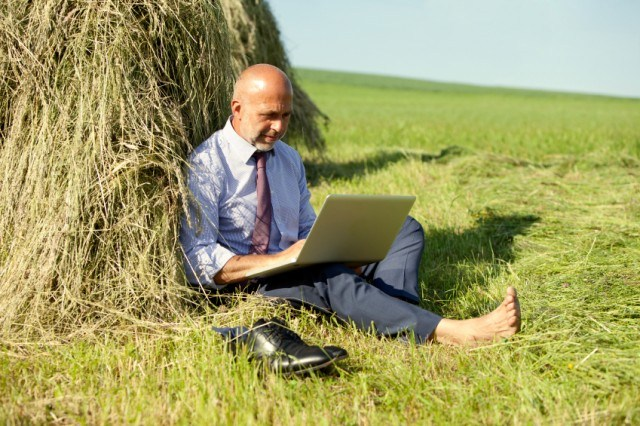 man on computer in field
