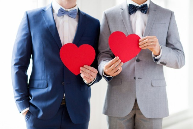 two men in suits holding paper hearts