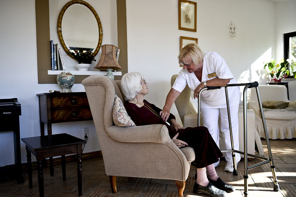 A social worker speaks to an old woman