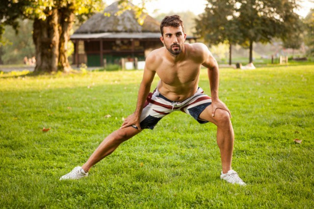 Man doing side lunges outside