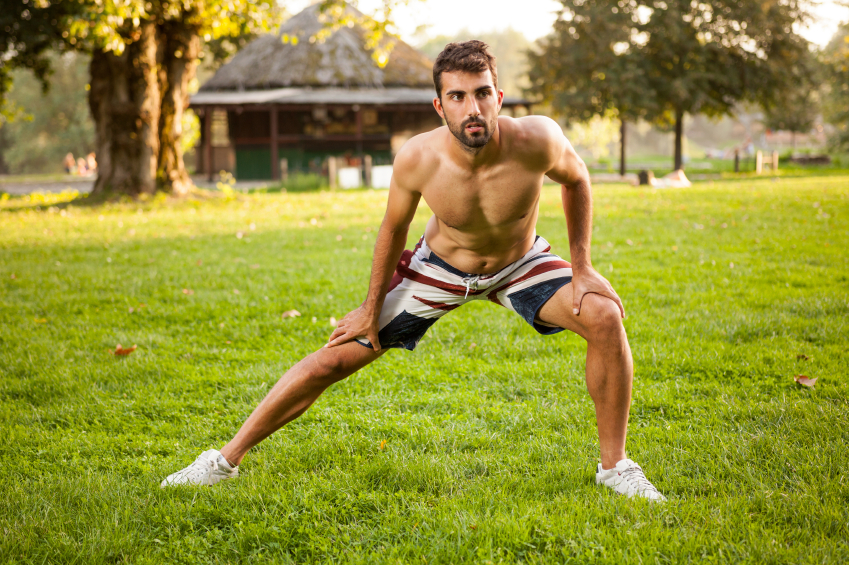man performing side lunge or stretch in the park