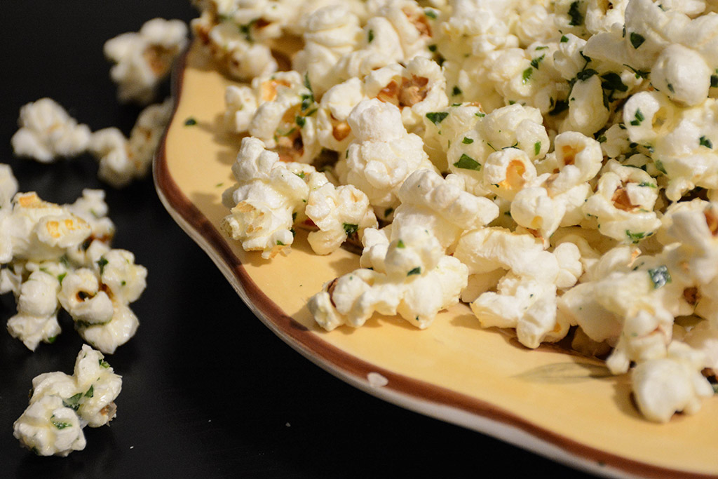 close up of Garlic Parmesan Popcorn with parsley in a yellow bowl