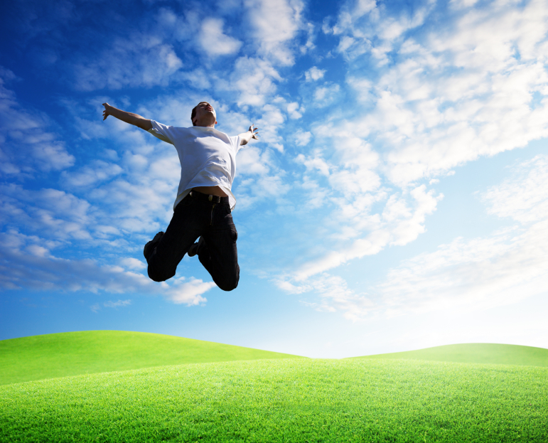 man jumping in a field with blue sky and clouds