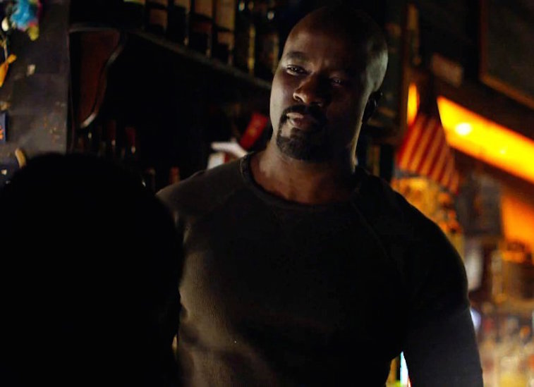 Luke Cage smiling, and wearing a brown long-sleeve shirt
