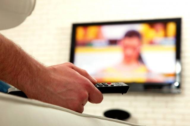 Man watching TV and holding a remote control