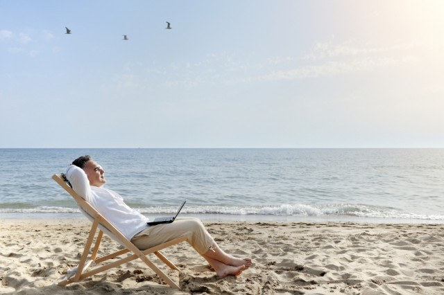 Man relaxing on the beach with laptop